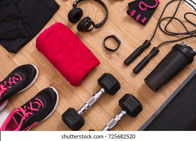 Female sport clothing and equipment top view. Set of fitness outfit and accessories for women on wood, active lifestyle, body care concept