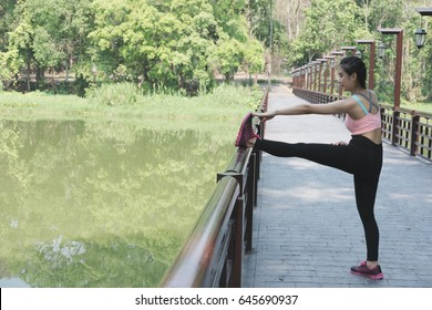 Female sport fitness athlete runner getting ready for jogging outdoors on forest path in spring or summer. Healthy young asian woman stretching before running or after exercise in the tropical park.