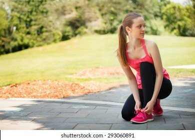 Female sport fitness runner getting ready for jogging outdoors on forest path in spring or summer.