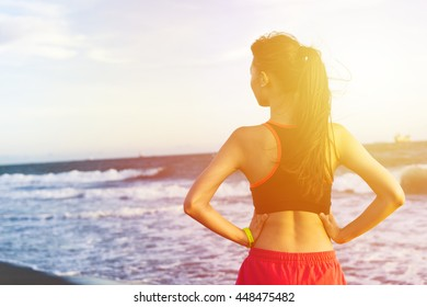 Female sport fitness runner getting ready for jogging outdoors on beach