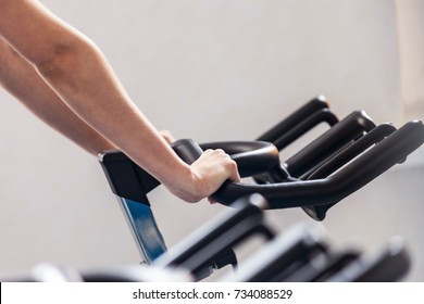 Female sportsman trains on a stationary bike. A female fitness instructor doing exercises. Fitness club gym training lifestyle commercial concept.