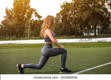 Female Sportsman Workout in Profile. Girl Stretching her Legs on Green Grass of Football Stadium Outdoor. Vintage Colours