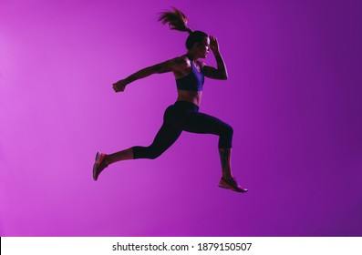 Female sprinter running on purple background. Portrait of woman with long stride while running.