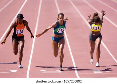 Female sprinters crossing the finish line at the end of a sprint race on a bright, sunny day at the track