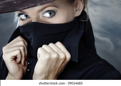 Female spy in hat with face covered by the coat collar