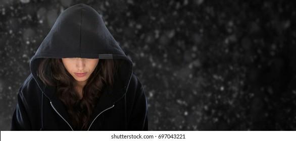 Female spy in hoodie against black background