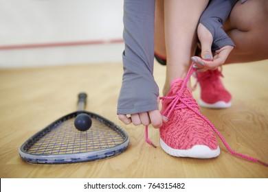 Female squash player tying sports shoe