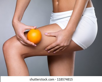 Female squeezes cellulite skin on her legs - close-up shot on white background