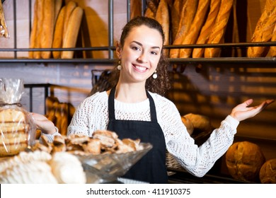 Female staff selling fresh pastry and baguettes in local bakery