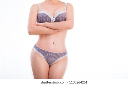 Female standing with arms and legs crossed, wearing gray underwear, isolated on a white background