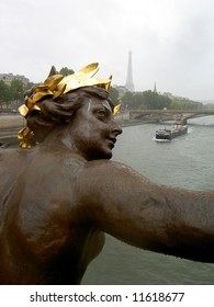 Female statue wearing a golden wreath, with the Eiffel Tower in the background and the Seine flowing underneath.