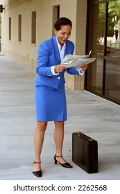 Female stock broker looking happy at the stock pages