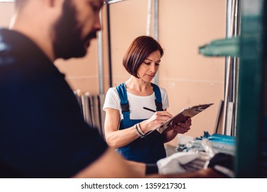 Female stock clerk controlling inventory with a help of warehouse worker