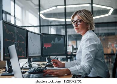 Weibliche Börsenmakler in formaler Kleidung arbeitet im Büro mit dem Finanzmarkt.