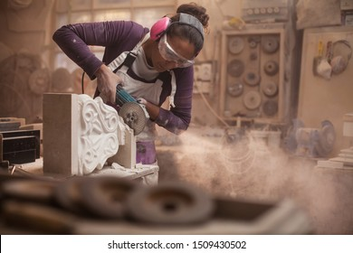 Female stonemason cutting a piece of white marble in a workshop, craftswoman grinding a sculpture with an angle grinder, women doing hard work concept
