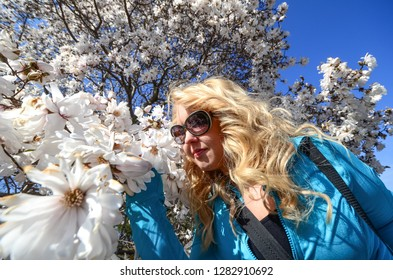Female stops to smell beautiful white flower blossoms on a tree during the spring