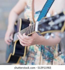 Female street musician playing guitar on sidewalk.