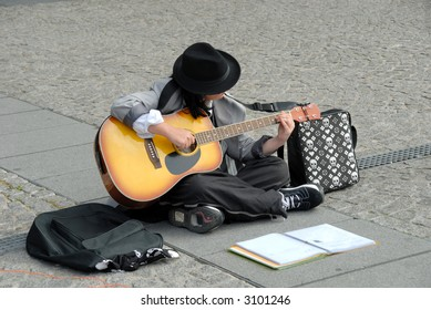 Female street performer, playing the guitar in paris on place pompidou in france