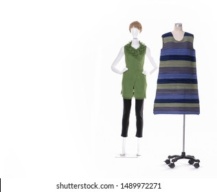 Female in striped sundress clothes and green clothes with black pants on two mannequins on white background,