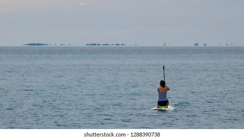 Female in striped swimsuit paddle boards on the ocean on the Caribbean Sea. Location: Hopkins, Belize