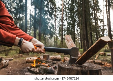 Female strong hands chop firewood with axe for bonfire. Powerful ax blow. Survival on camping trip. Harvesting wood in forest. Camp wild tourists. Splitting logs with sharp hatchet. Young woodcutter