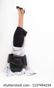 Female stuck in garbage bin upside down. Female office worker formaly dressed standing upside down in trash bucket with paper outside of it. Isolated on white background.