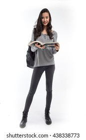 Female student with a backpack holding a book and smiling on white background