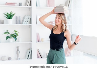 Female student balancing books on top of her head. Beautiful blonde girl keeps a stack of books on her head. The concept of education, courses, examinations, homework, list of books to read.