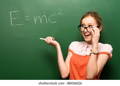 Female student by chalkboard with e=mc2