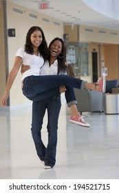 Female student carrying her friend and laughing