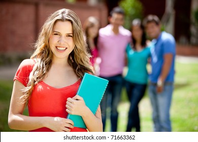 Female student carrying notebooks outdoors and smiling