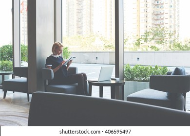 Female student is checking e-mail on digital tablet, while is waiting file download on laptop computer. Businesswoman is ordering on-line car via touch pad, while is sitting with net-book in cafe