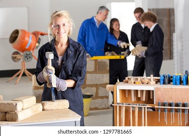 Female student with chisel learning bricklaying at technical college smiling at camera