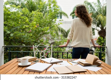 Female student enjoying view from balcony before continue the work, her messy workplace on the foreground