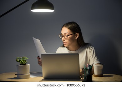 Female student getting ready for exam, reading paper handout material, working at laptop, or preparing presentation at night under lamp light. Woman taking online business course in small home office