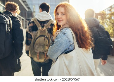 Female student glancing back while going for a class in college. Girl walking with friends going for class in high school.