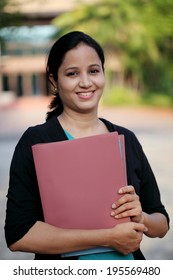 Female student holding folder at college campus