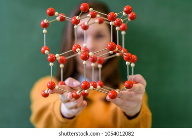 Female student holding molecular structure model. Science class concept.