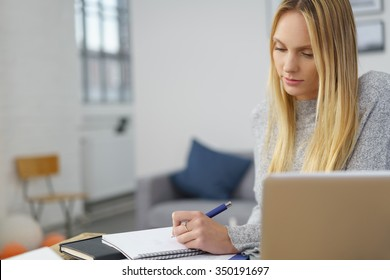 Female student at home with Laptop and Paperwork making Some Notes