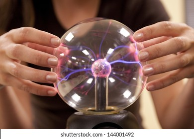 A female student investigates the properties of a plasma ball.