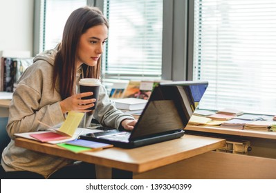 Female student learning online, in library