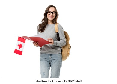 female student looking at camera and holding canadian flag with notebook isolated on white