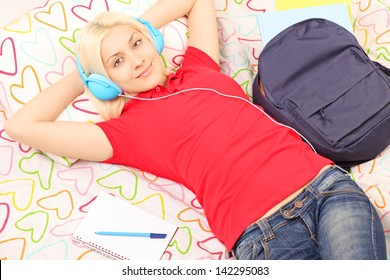 Female student lying in bed with backpack and notebook and listening to music