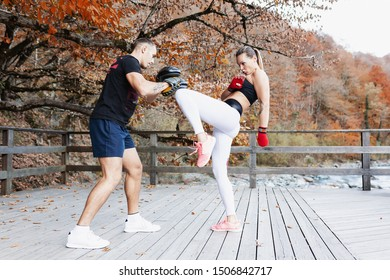 Female student and a male martial arts coach are engaged in kickboxing in protective gear in the open air. Concept of sports and stamina. Translation: Konstantin