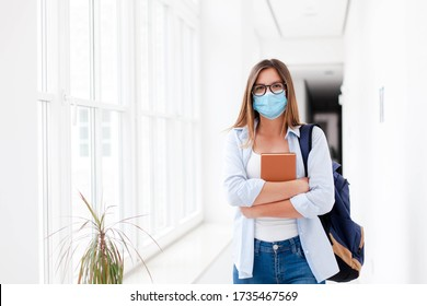 Female student in mask indoors going to exams in high school. Young woman in empty university. Girl with backpack and book in college corridor. Social distancing during quarantine.
