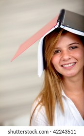 Female student with a notebook on her head smiling
