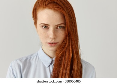 Female student or office worker with freckles and loose ginger hair wearing shirt looking at camera with serious expression, posing isolated at white studio wall with copy space for your content