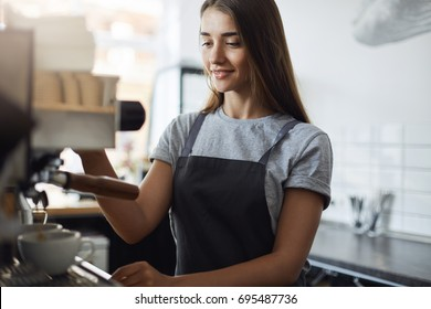 Female student on her summer job serving coffee working as a in a local pastry shop