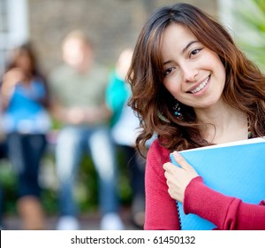 Female student outdoors holding a notebook and smiling