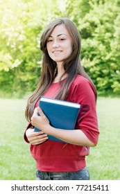 Female student outdoors portrait with book.